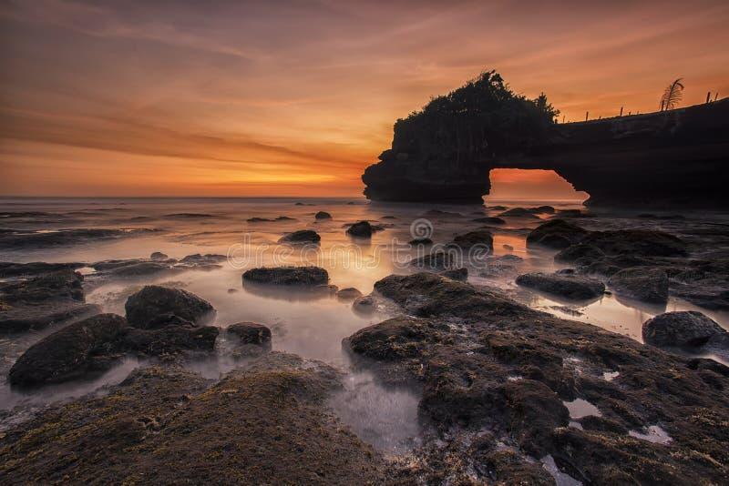 Cieli Arancio E Gialli Di Tramonto Sopra Grey Seashore Rocks E L'oceano Calmato Dominio Pubblico Gratuito Cc0 Immagine