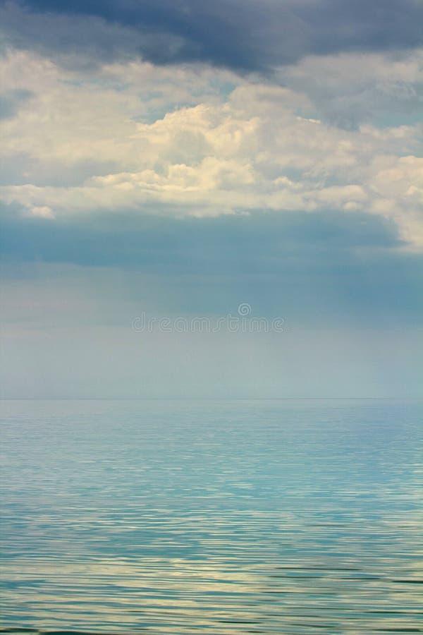 Cieli tristi sopra superficie rispecchiata del mare immagini stock libere da diritti