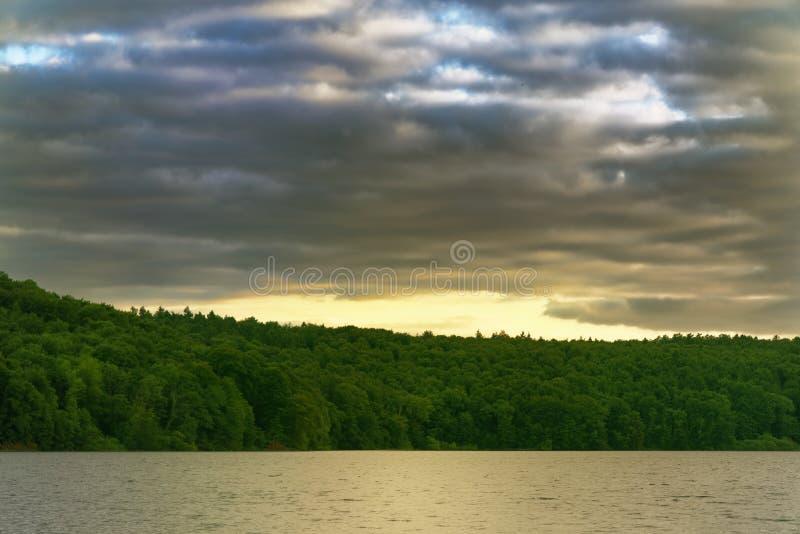 Cielo amarillo romántico en la puesta del sol sobre el lago con el bosque en la costa costa fotografía de archivo libre de regalías