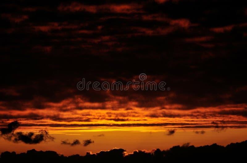 Cielo anaranjado con las nubes oscuras pesadas fotos de archivo