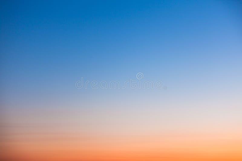 Cielo anaranjado y azul claro de la puesta del sol fotografía de archivo