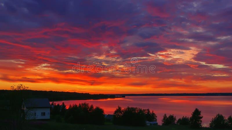 Cielo ardiente dramático de la puesta del sol de la noche sobre el lago foto de archivo libre de regalías