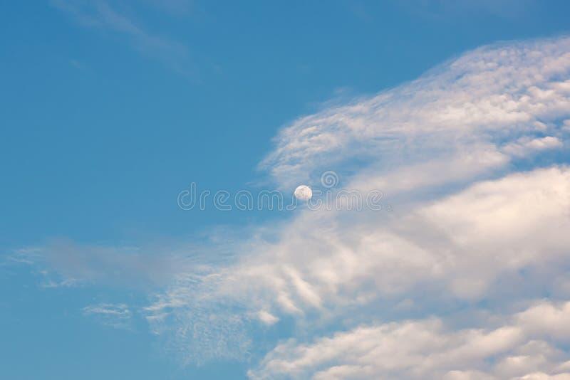 Cielo azul brillante de la mañana con la media luna y las nubes La luna y las nubes en el cielo del verano fotografía de archivo