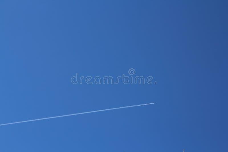 Cielo azul brillante en el cual el avión vuela dejando un rastro foto de archivo libre de regalías