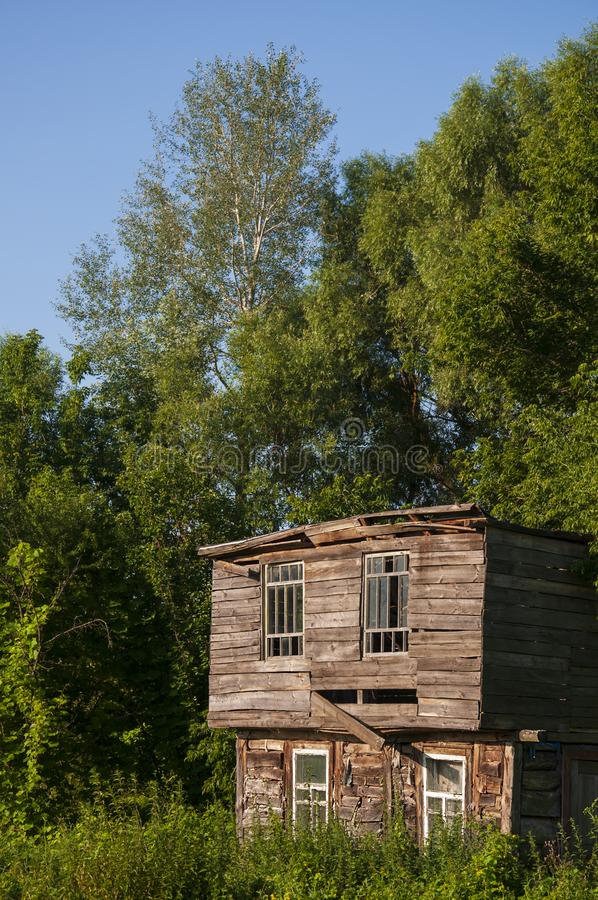 Cielo azul claro en el verano caliente sobre la casa abandonada vieja construida de la madera lejos en los árboles del Forest Gre imagen de archivo