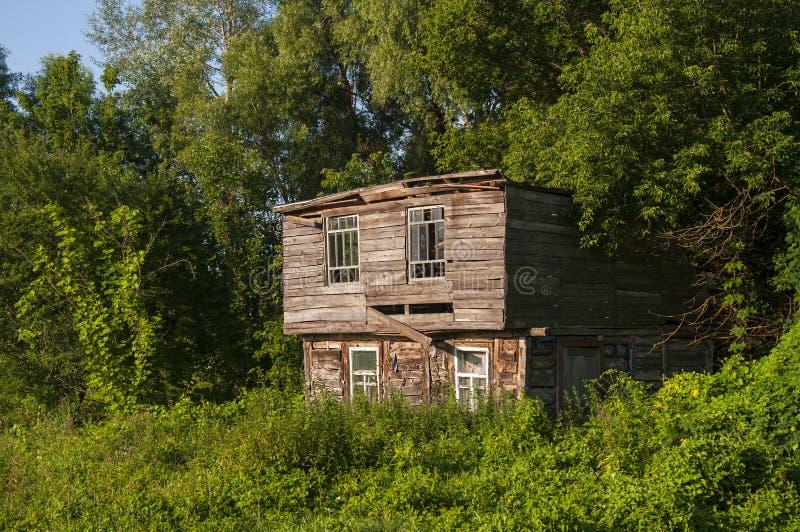 Cielo azul claro en el verano caliente sobre la casa abandonada vieja construida de la madera lejos en los árboles del Forest Gre imagen de archivo libre de regalías
