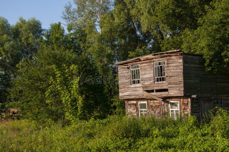 Cielo azul claro en el verano caliente sobre la casa abandonada vieja construida de la madera lejos en los árboles del Forest Gre foto de archivo