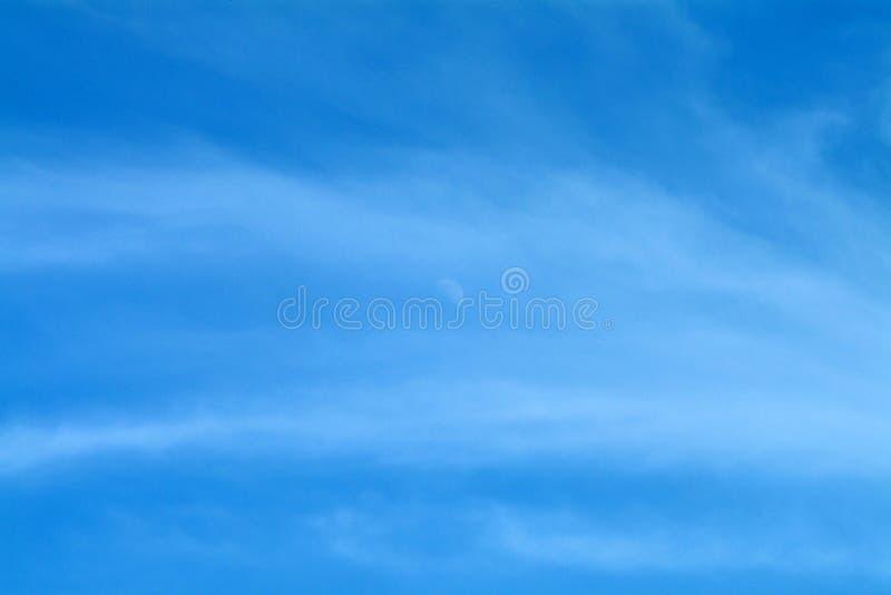 Cielo azul con la luna y las nubes Wispy fotos de archivo