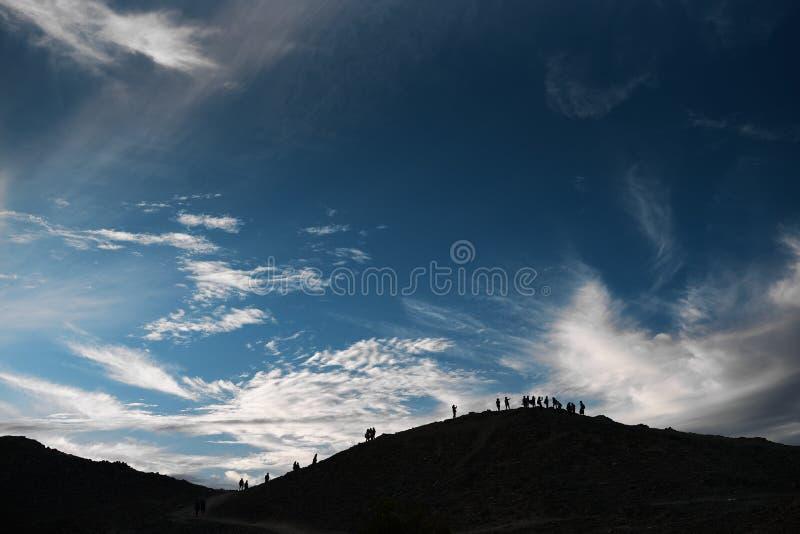 Cielo azul con las montañas de la colina de las nubes con contornos de la gente fotos de archivo libres de regalías