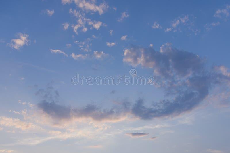 Cielo azul con las nubes blancas en forma del arco con el colorante rojo por puesta del sol en sol por la tarde imagenes de archivo
