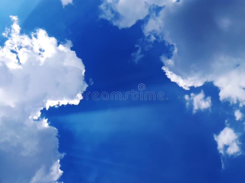 Cielo azul con las nubes y el sol imagen de archivo