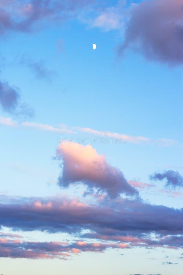 Cielo azul de la puesta del sol con las nubes del creciente y del purpure imagen de archivo