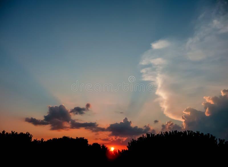 Cielo azul dramático de la puesta del sol con Sun rojo en el horizonte y las nubes oscuras en el contraste imagenes de archivo