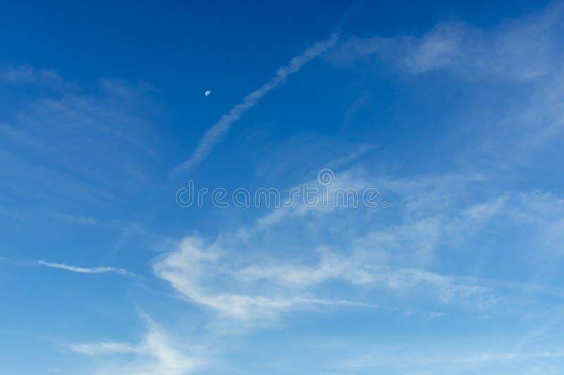 Cielo azul hermoso con la luna y velos blancos, finos, translúcidos y fibrosos interesantes de los cristales de hielo en la sol d imagen de archivo