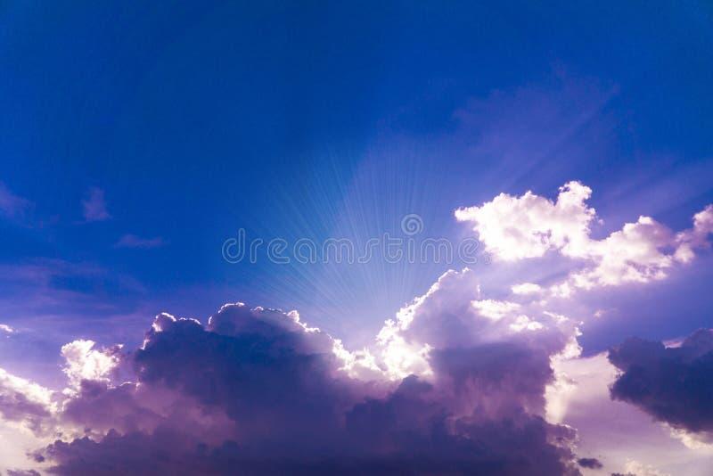 Cielo azul hermoso con los rayos solares que suben de detr?s las nubes stock de ilustración
