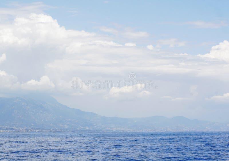 Cielo azul nublado que se va para el horizonte sobre una superficie azul del mar foto de archivo