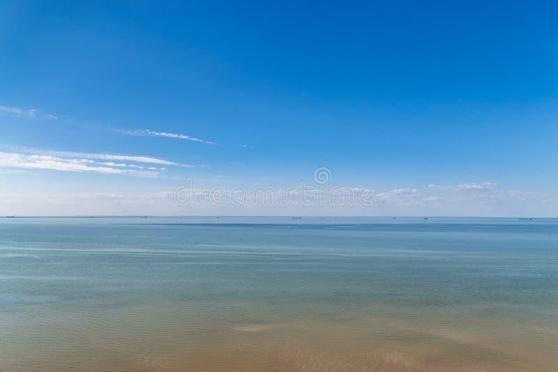 Cielo azul nublado que se va para el horizonte sobre una superficie azul del mar fotos de archivo libres de regalías