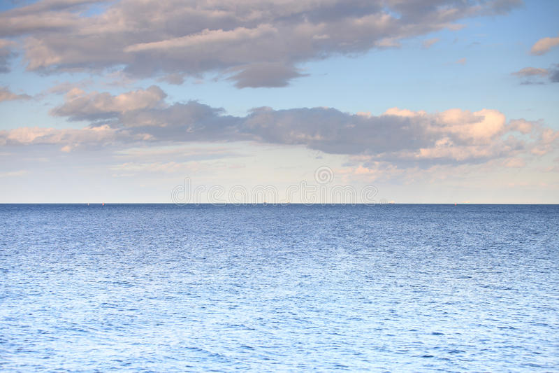 Cielo azul nublado que se va para el mar superficial azul del horizonte imagen de archivo