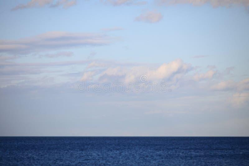 Cielo azul nublado que se va para el mar superficial azul del horizonte foto de archivo libre de regalías