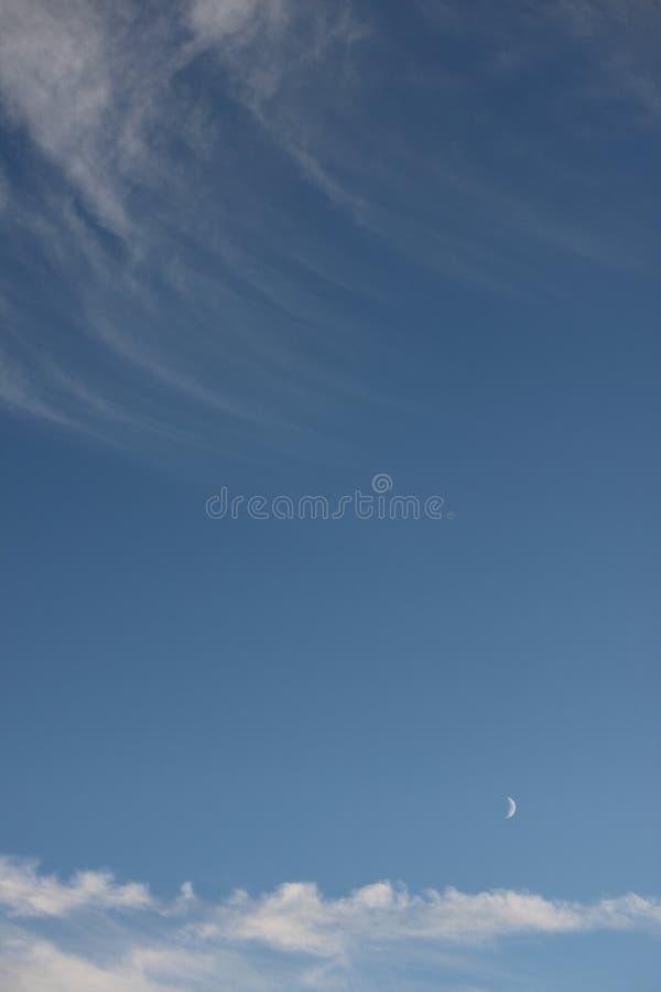 Cielo azul pacífico con la nube y la luna blancas arrebatadoras fotografía de archivo