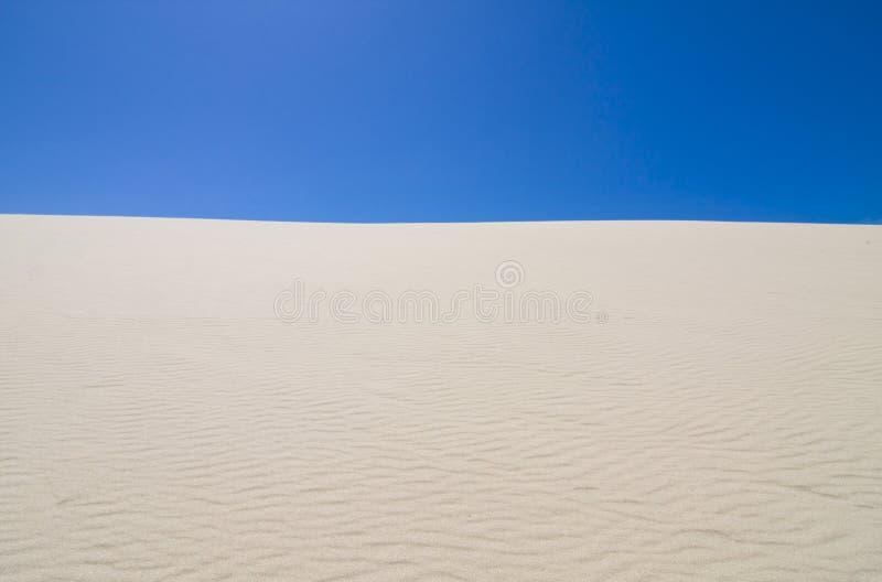 Cielo azul profundo contra las dunas de arena onduladas imágenes de archivo libres de regalías
