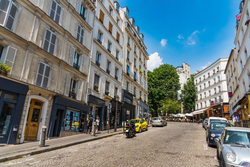 Cielo azul sobre una calle pintoresca en la vecindad de Montmartre fotos de archivo
