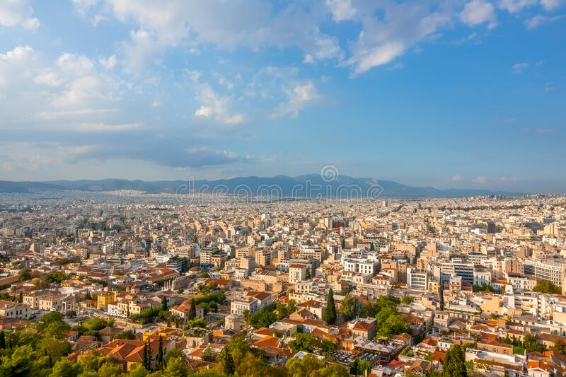 Cielo azzurro con nuvole sui tetti di Atene immagine stock