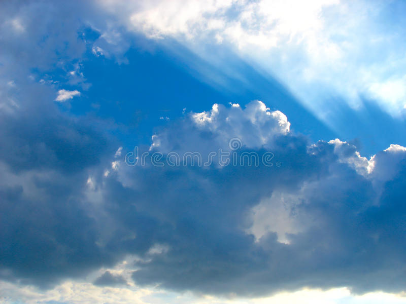 Cielo blu con i raggi del sole attraverso le nubi immagine stock