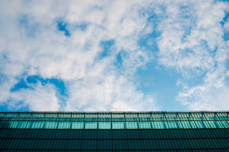 Cielo blu con le nuvole bianche e la parete di vetro del fondo geometrico del modello Copi lo spazio per testo immagini stock libere da diritti