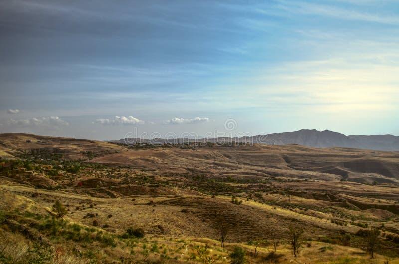 Cielo blu di autunno sopra una valle collinosa con i villaggi ed i campi nella cresta di Geghama delle montagne fotografia stock libera da diritti