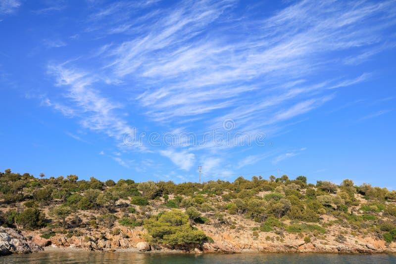 Cielo blu di ora legale bello sopra la costa dell'isola di Poros, Grecia fotografia stock