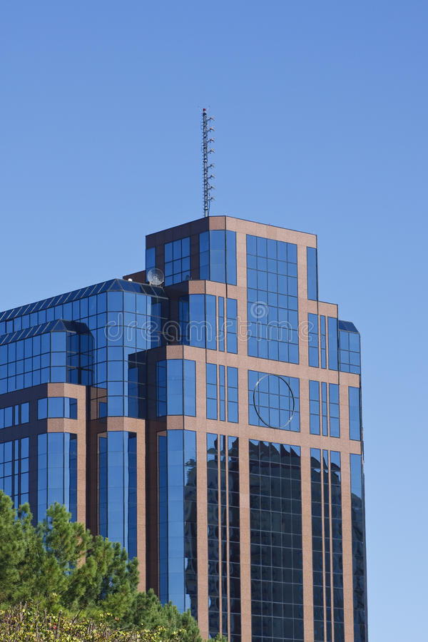 Cielo blu di riflessione rosso dell'ufficio di vetro e della pietra fotografia stock libera da diritti