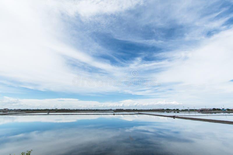 Cielo blu e nuvole bianche, riflessioni dell'acqua nell'agricoltura del sale fotografia stock