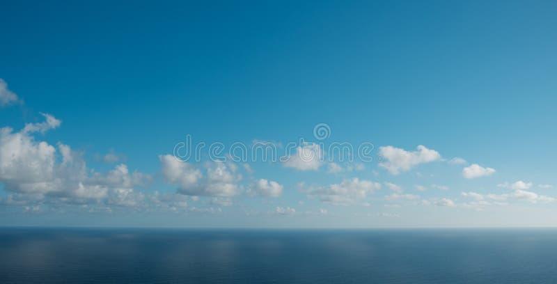 Cielo blu sopra l'orizzonte dell'oceano con le nuvole immagini stock libere da diritti