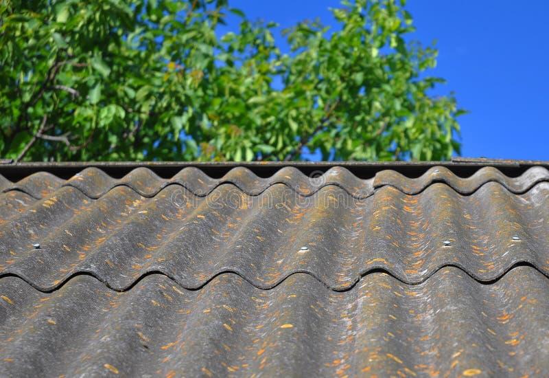 Cielo blu sopra le vecchie mattonelle di tetto dell'amianto pericoloso capaci di usare come fondo strutturato fotografia stock