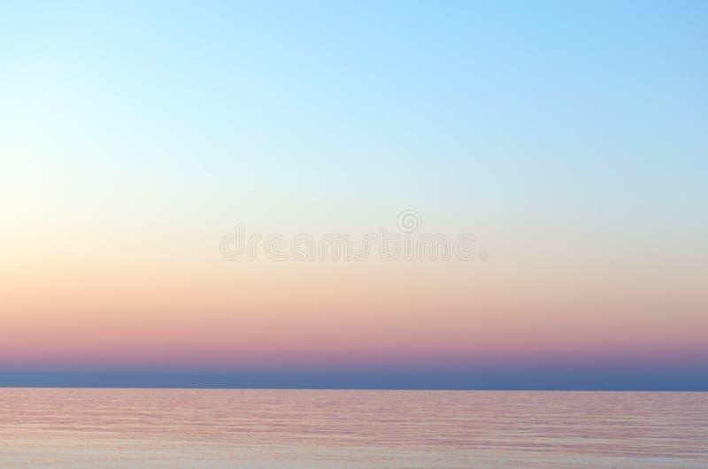 Cielo claro de la puesta del sol Fondo de la pendiente en colores en colores pastel Puesta del sol sobre el mar imagen de archivo libre de regalías