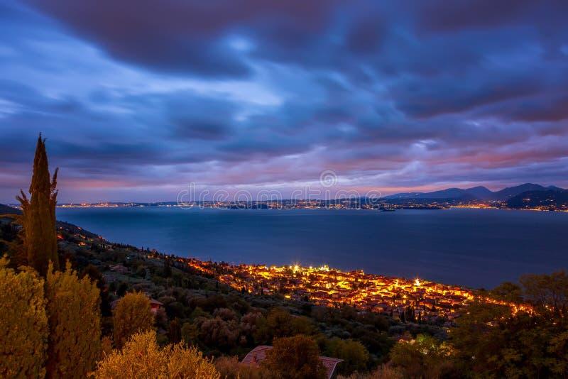 Cielo colorido fantástico con puesta del sol imponente y pequeñas ciudades iluminadas en región del lago Garda, Véneto, Italia, E imagen de archivo libre de regalías