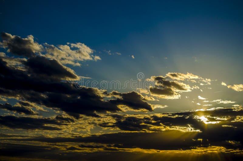 Cielo con le nuvole e stabilire del sole Tramonto con i raggi del sole fotografia stock