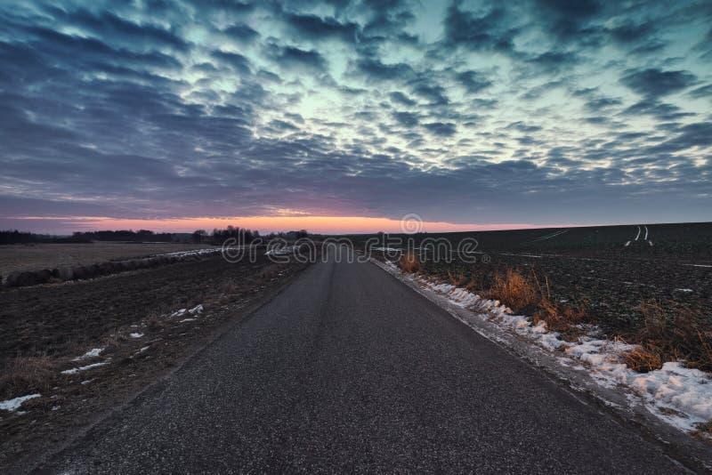 Cielo crepuscolare sopra Asphalt Road vuoto all'inverno immagine stock libera da diritti