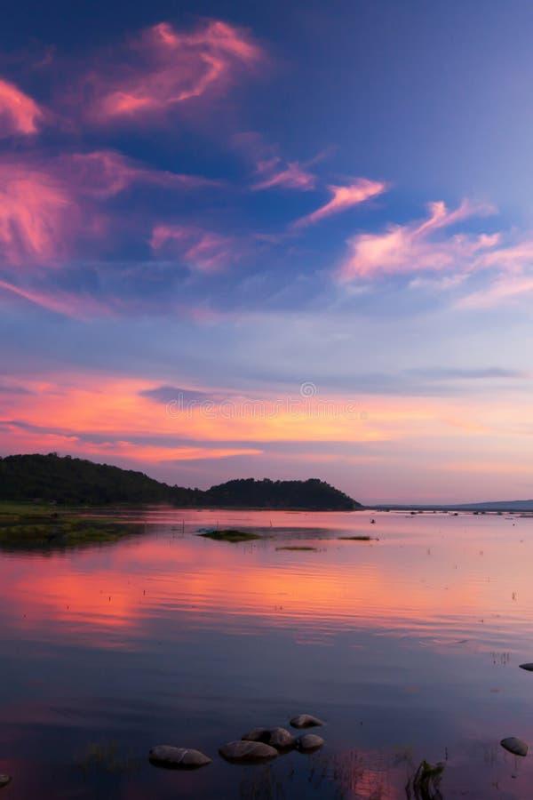 Cielo crepuscular hermoso sobre un lago tropical, suavemente nubes rosas claras contra el cielo azul en la oscuridad foto de archivo