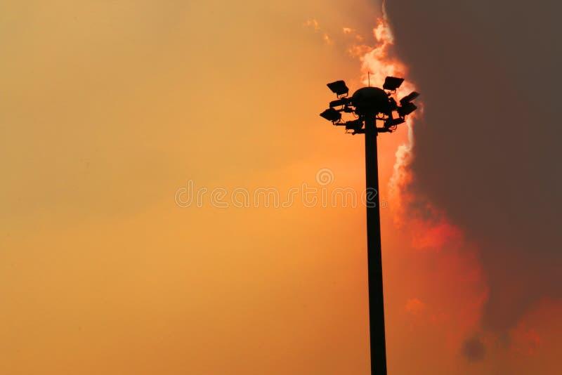 Cielo de la naranja del againt de los posts de la electricidad imagen de archivo libre de regalías