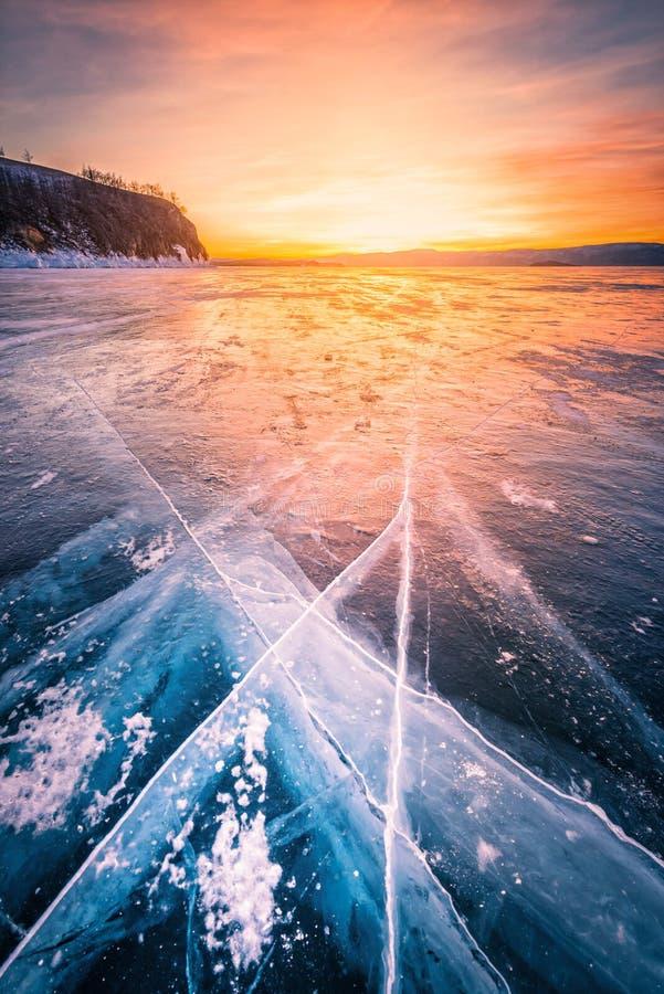 Cielo de la puesta del sol con hielo de fractura natural sobre el agua congelada en el lago Baikal, Siberia, Rusia imagen de archivo