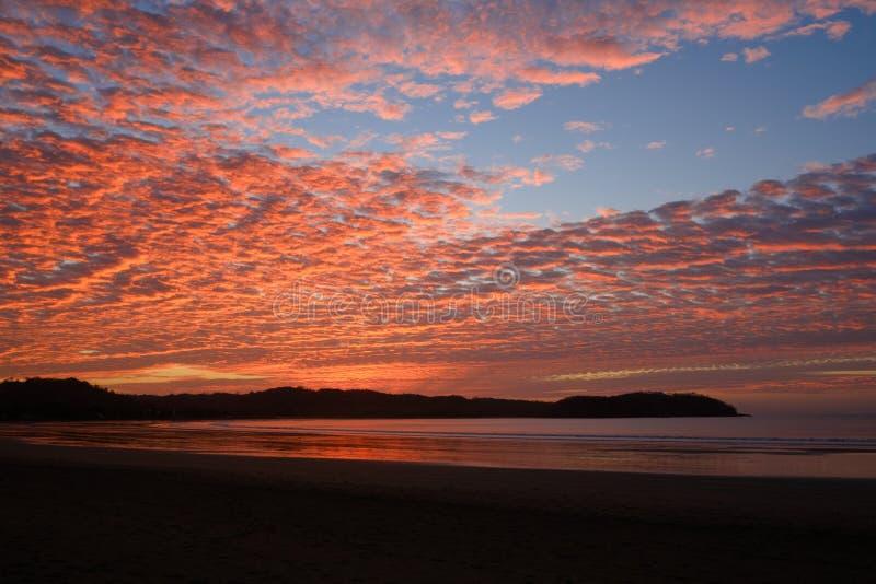 Cielo de la puesta del sol con las nubes coloridas sobre el océano en la playa - fotografía de archivo