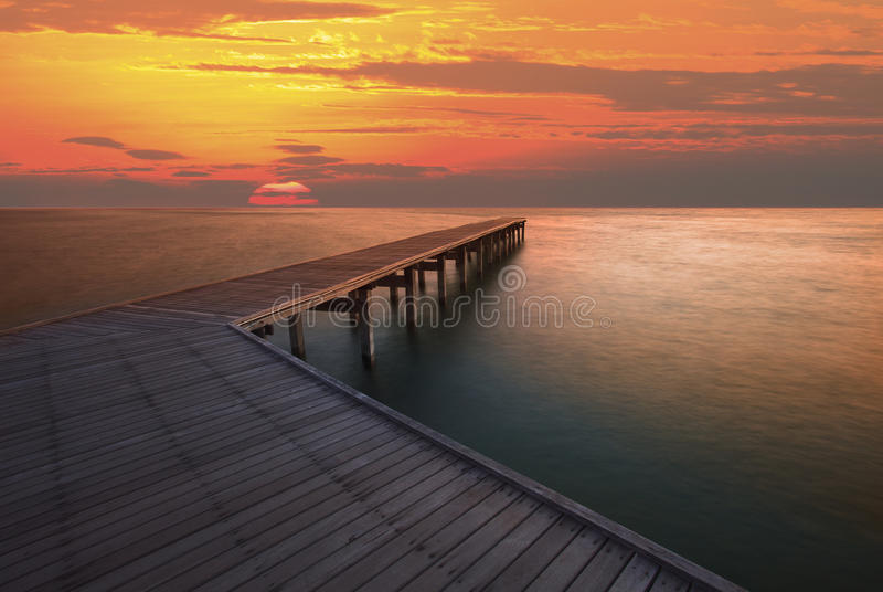 Cielo de la subida de Sun y embarcadero de madera viejo del puente foto de archivo libre de regalías
