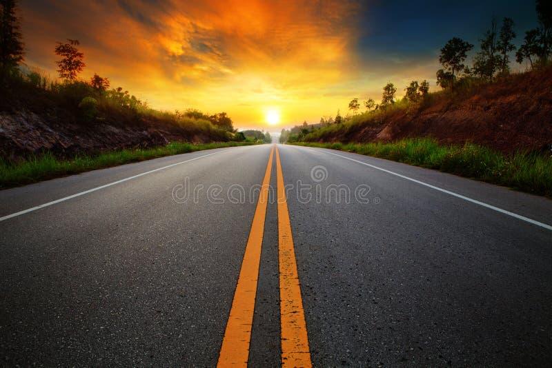 Cielo de levantamiento del sol hermoso con el camino de las carreteras del asfalto en el sce rural imagen de archivo