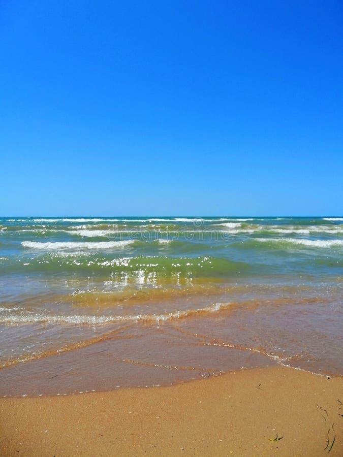 Cielo despejado, ondas y playa arenosa foto de archivo libre de regalías