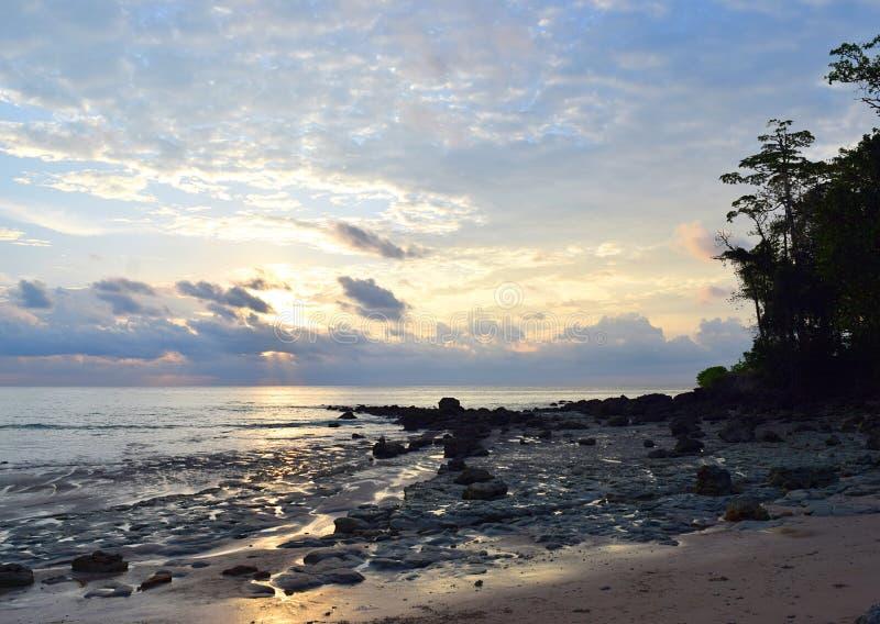 Cielo di mattina con il sol levante dietro le nuvole all'orizzonte, oceano e Rocky Beach - Sitapur, Neil Island, andamane Nicobar immagini stock libere da diritti