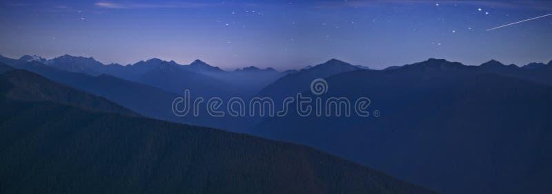 Cielo di notte e catena montuosa olimpica con la stella cadente fotografia stock