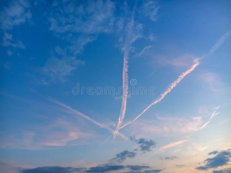 Cielo di sera con tre tracce attraversate di aerei e di luna crescente fotografia stock libera da diritti