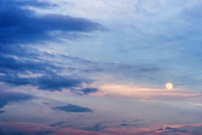 Cielo di sera tardi con la luna piena e le nuvole porpora immagini stock libere da diritti